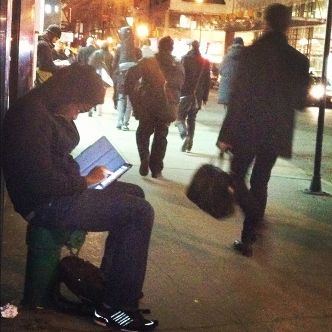 Guy sitting on sidewalk with iPad