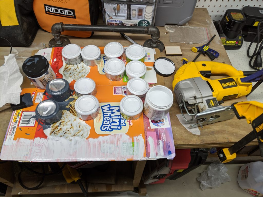 A number of cut aluminum cans turned upside-down and painted white. A jigsaw sits to the right of the cans.