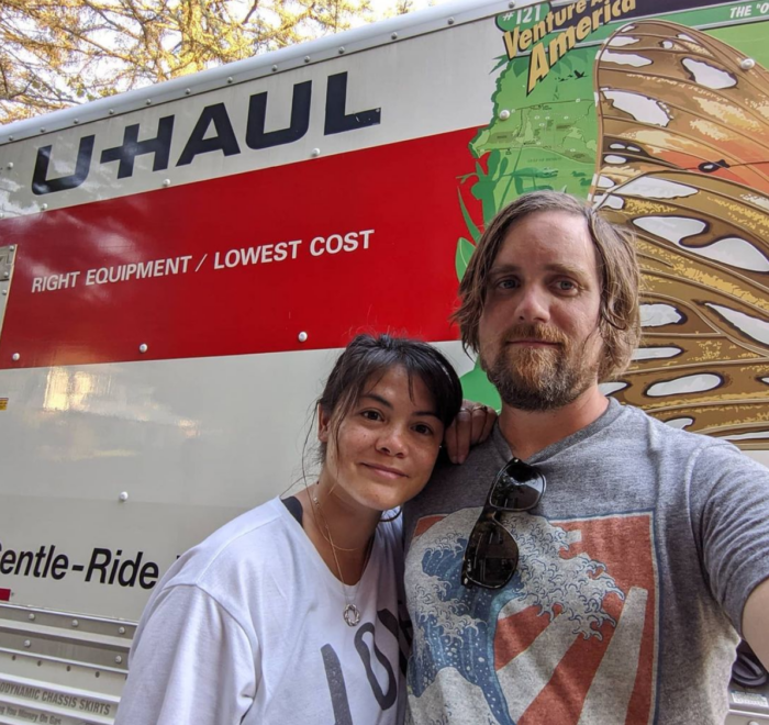 Melissa and Brad standing in front of a Uhaul truck