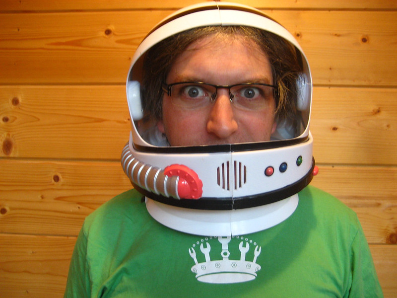 Jeremy Keith wearing glasses and a toy space helmet with a green t-shirt